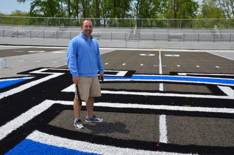NEW TURF — Mark Kowalski, director of operations for the Harrison Hills City School District, shows off the artificial turf that has been installed at Wagner Field. - Kim North