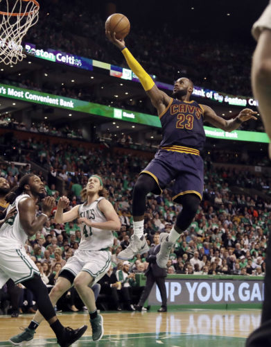 FILE - In this May 25, 2017, file photo, Cleveland Cavaliers forward LeBron James (23) soars to the basket over Boston Celtics forward Jae Crowder, left, and center Kelly Olynyk (41) during the second half of Game 5 of the NBA basketball Eastern Conference finals in Boston. As James and the Cavaliers prepare to face the Golden State Warriors and their collection of All-Stars in the NBA Finals, he is leaning on the experience he has had in previous postseason matchups against great San Antonio and Boston teams. (AP Photo/Elise Amendola, File)