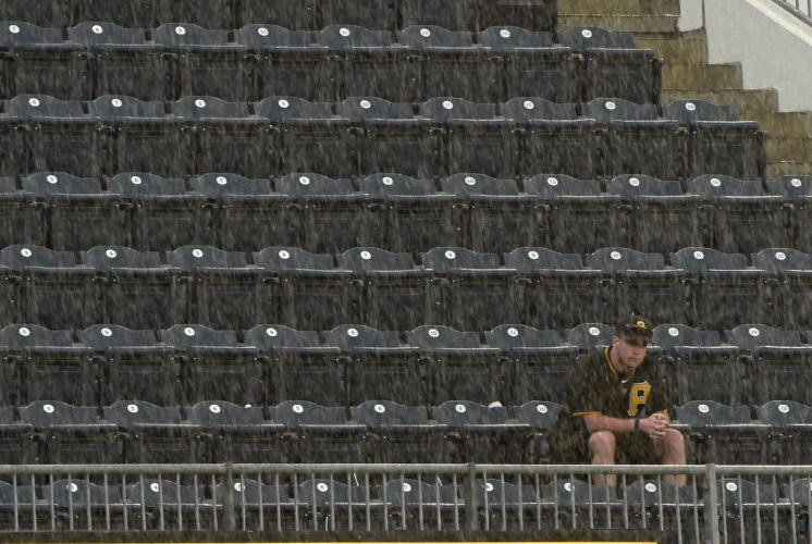 A Pittsburgh Pirates fan sits through a rain storm in the 11th inning of a baseball game against the Arizona Diamondbacks in Pittsburgh, Wednesday, May 31, 2017. (AP Photo/Fred Vuich)