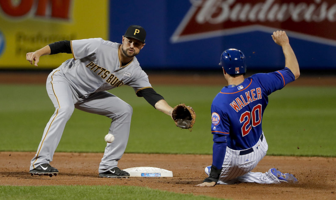 Pittsburgh Pirates shortstop Jordy Mercer (10) reaches for a throw to put the tag on New York Mets' Neil Walker (20) who was attempting to steal second base during the third inning of a baseball game, Saturday, June 3, 2017, in New York. Walker was out on the play. (AP Photo/Julie Jacobson)