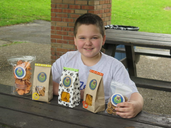 BISCUITS FOR DOGS — Zeb Helmick, 9, of Bethlehem shows off the dog biscuits he is baking, marketing and selling at the farmers' market outside St. Michael Catholic Church in Wheeling. -- Joselyn King