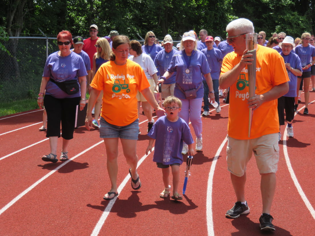 LEADING THE WAY — Six-year-old Peyton Geary, who was born with leukemia, walked with his parents, Jake and Melissa Geary, during the cancer survivors' opening lap of Saturday's 22nd-annual Steubenville Area Relay for Life to benefit the American Cancer Society.  -- Janice Kiaski