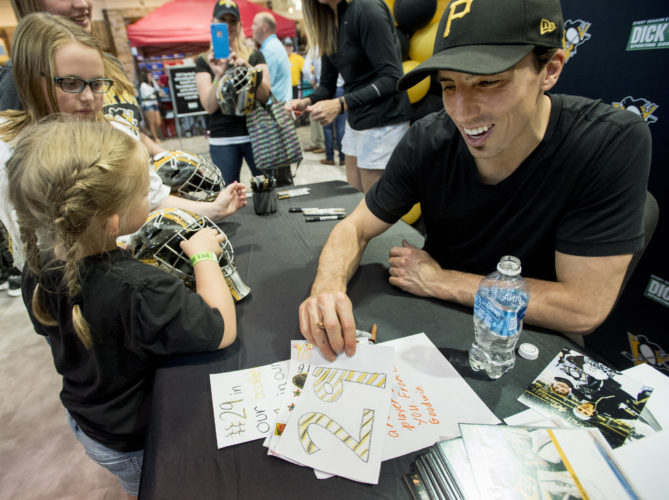 ONE FINAL GESTURE — A group of fans give handwritten cards to former Pittsburgh Penguins goaltender Marc-Andre Fleury during an autograph session Tuesday at Dick's Sporting Goods in Cranberry Township, near Warrendale, Pa. (AP Photo)
