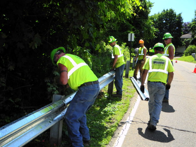 NEW PRODUCT ON DISPLAY — Crews with Green Acres Contracting of Scottdale, Pa., on Wednesday installed along Marquette Avenue in Follansbee about 1,800 feet of guardrail, including several sections coated with ZAM, a new coating produced by Wheeling-Nisshin Steel said to be at least three times more resistant to corrosion. Officials said sections of ZAM coated guardrail were alternated with galvanized steel sections to show the difference between the durability -- Warren Scott