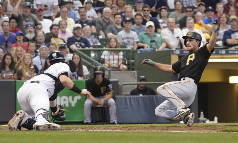TAGGING ALONG — Milwaukee Brewers catcher Jett Bandy tags out Pittsburgh Pirates' Adam Frazier at home during the eighth inning Thursday in Milwaukee. (AP Photo)