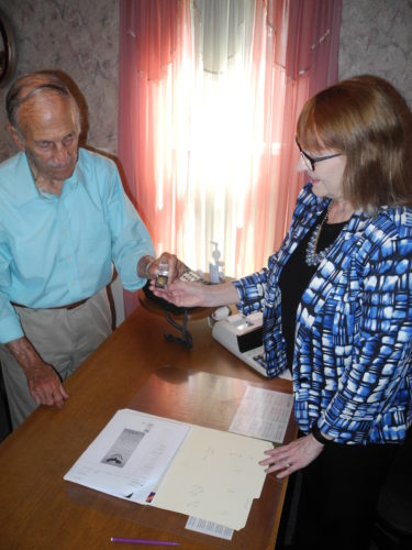 VETS TO BE HONORED — Tony Paesano, president of the Follansbee Chamber of Commerce, and Debbie Puskarich, chamber executive director, look at one of the pins to be presented to Brooke County veterans of the Vietnam War at a dinner to be held in their honor on Aug. 15 at Vito's 2. -- Warren Scott