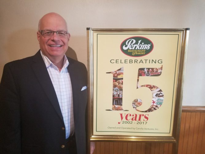 Perkins Restaurant and Bakery owner Frank Carolla shows off artwork specially commissioned to recognize Perkins' 15 years of community involvement in the local area. — Contributed