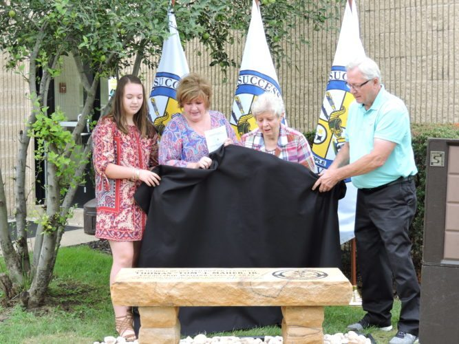 Family, friends and co-workers of former Weirton Finance Director Thomas J. Maher Jr. on Tuesday unveiled a bench dedicated in Maher's memory. Assisting with the unveiling were, from left, Maher's niece, Alexis Humphrey; sister Michele Humphrey; mother Katherine Maher; and Weirton Mayor Harold Miller. Maher died last fall following a lengthy illness. — Craig Howell