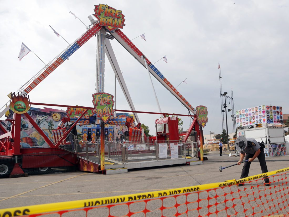 FATAL RIDE — An Ohio State Highway Patrol trooper removes a spike Thursday from in front of a ride that was the scene of a fatal accident Wednesday. The fair was open Thursday but the rides were closed while the investigation continued.  -- Associated Press