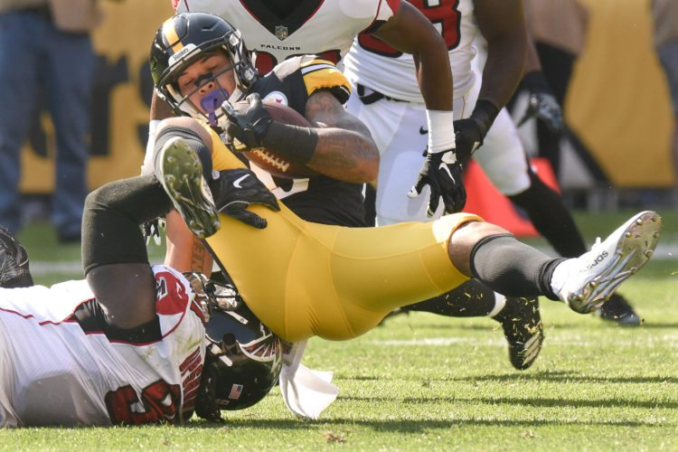 TACKLE — Steelers' running back James Conner is tackled by Atlanta defensive end Courtney Upshaw during Sunday's game at Heinz Field. -- Asssociated Press