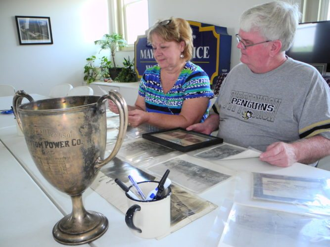 ANNIVERSARIES — Beech Bottom Mayor Becky Uhlly and Councilman Ted Westfall study some old photos related to the Windsor Power Plant, which began operations on Aug. 19, 1917. Also before them is a trophy bearing the records of the plant's adult baseball teams in 1924 and 1925. Village officials are working with a group of volunteers to mark the plant's anniversary while also celebrating its own 100th anniversary with a community picnic on Sept. 2 and the 100th anniversary of an airfield near the village — home to the West Virginia Flying Corps — on Sept. 30. -- Warren Scott