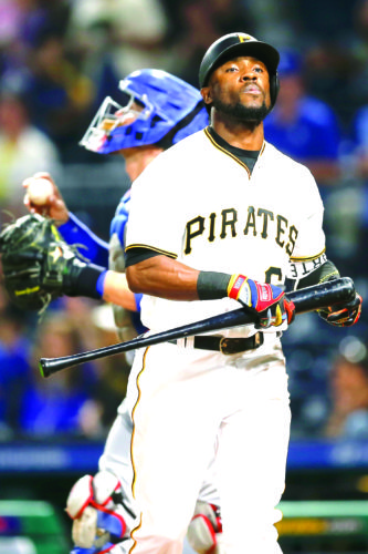 GAME OVER — Pittsburgh Pirates' Starling Marte heads to the dugout after striking out as Los Angeles Dodgers catcher Yasmani Grandal holds the ball at the end of a game Tuesday in Pittsburgh. (AP Photo)