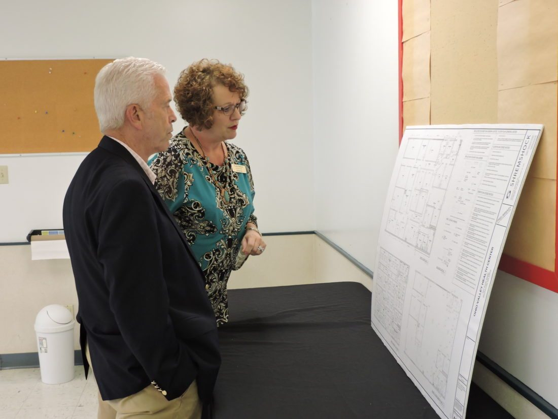 STUDYING BUILDING PLANS — U.S. Rep. Bill Johnson, R-Marietta, and Trudy Wilson, executive director of the Ohio Valley Health Center, look at a detailed building plan for the transformation of the former Neighborhood House day care center into the new home for the Ohio Valley Health Center. Johnson met Wednesday afternoon with Wilson, several staff employees and members of the center's board of directors. -- Dave Gossett
