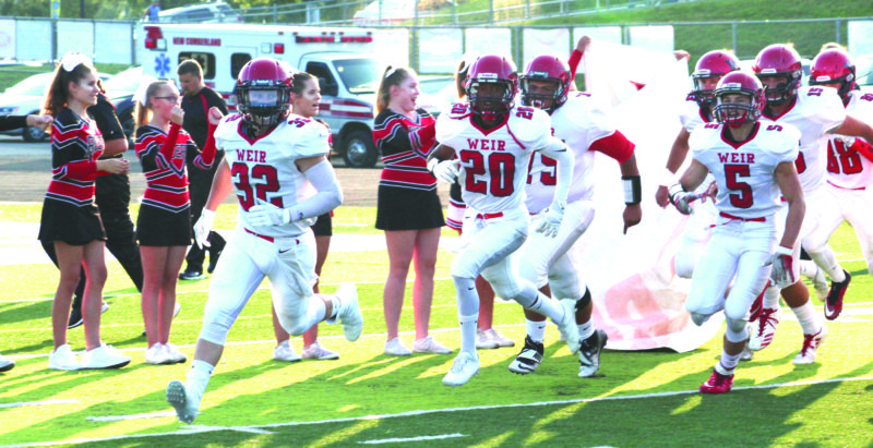 THROUGH THE SMOKE — Weir's Tyler Mack (32), Jaylon Bridges (20), Chad Custer (5) and more come out of the tunnel before its matchup with Oak Glen on Friday. (Photo by Joe Catullo)