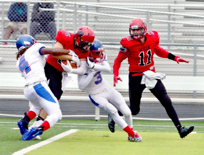 BULLDOZING — Weir's Tyler Mack fights for yards against Anacostia on Friday. (Photo by Michael D. McElwain)