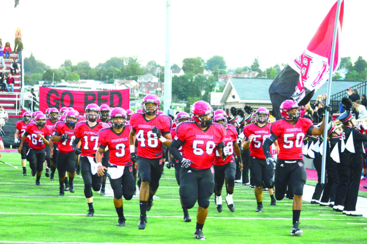 BIG CHALLENGE — The Steubenville football team runs on the field before its matchup with St. Joseph on Friday. (Photo by Michael D. McElwain)