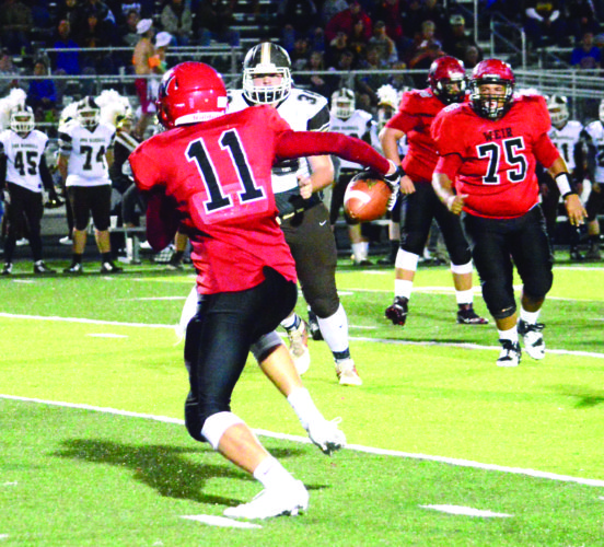 FINDING ROOM — Weir's Reed Reitter rushes while Mason Rice (75) watches against John Marshall on Friday. (Photo by Micheal D. McElwain)