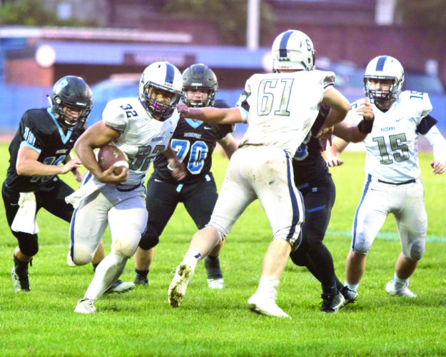 BREAKING TACKLES — Madonna's Donavan Kirby rushes while Zak Tokash (61) blocks against Bridgeport on Friday. (Contributed)