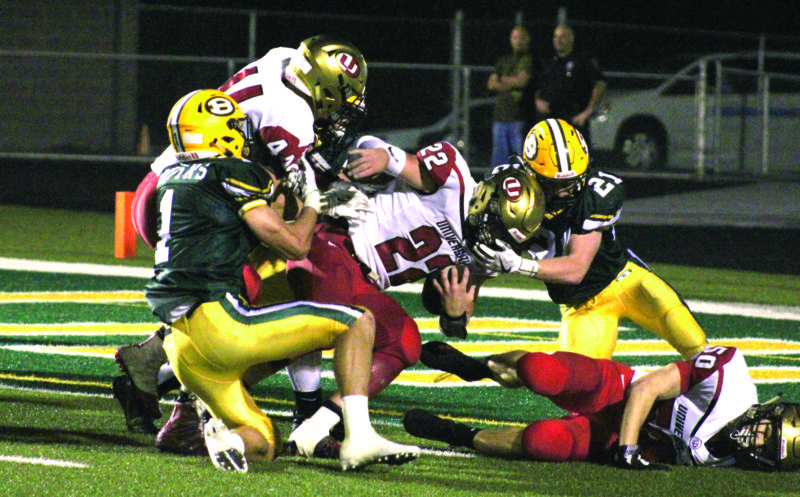 GOAL LINE STAND — Brooke's Ethan Secrist (1) and C.J. Helms (21) attempt to tackle University's Trevor Barnhart on a two-point coversion Friday night. (Photo by Joe Catullo)