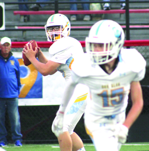LOOKING FOR NO. 15 — Oak Glen's Nick Chaney passes to Micahel Lemley (15) against Steubenville Catholic Central on Sept. 2. (Photo by Joe Catullo)
