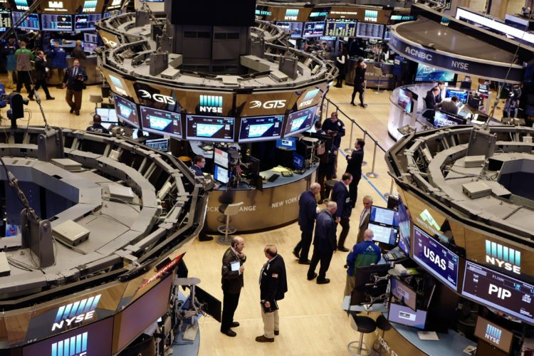STOCK TRADERS — Traders work the floor at the New York Stock Exchange. The stock market is at a record, and no one seems to care. Investors are on pace to pull more money out of U.S. stock funds than they put in for a third straight year, and for the eighth time in the last decade. That hesitance to buy is actually an encouraging sign to many investors and has some Wall Street watchers saying stocks can avoid a downturn in the near term.