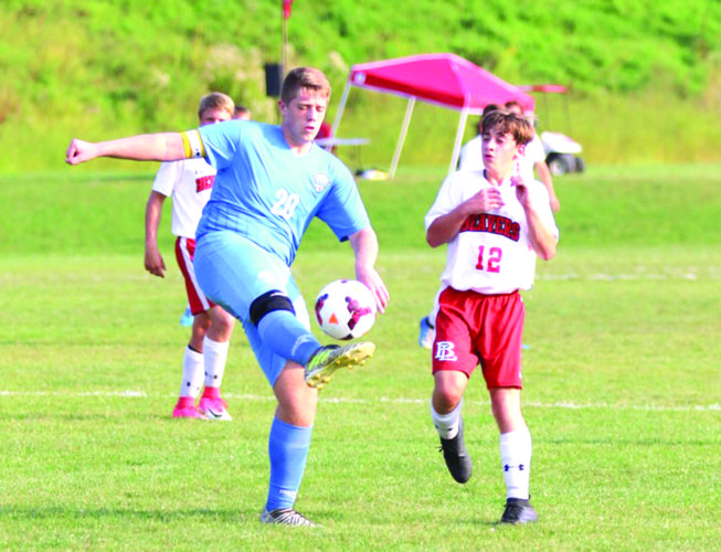 HIGH KICK — Oak Glen's Chance Provenzano kicks the ball in front of Beaver's Zack Smith on Monday. (Photo by Jimmy Joe Savage)