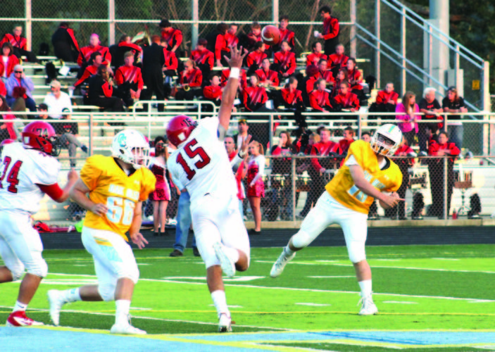 THROUGH A TIGHT WINDOW — Oak Glen's Nick Chaney completes a pass over Weir's Tyler Komorowski while Ty Biela (66) looks to block on Aug. 25 (photo by Joe Catullo).