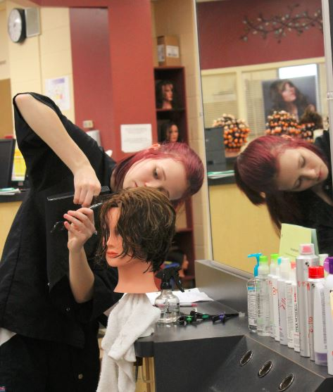 HONING SKILLS — Senior cosmetology student Gabby Lewis, a senior cosmetology student at the Jefferson County Joint Vocational School,  practices razor cutting on a mannequin. Her class is currently accepting clients from the general public.