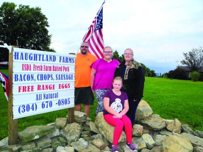 Joe and Lisa Haught have expanded their Wellsburg farm to include pork products and free range eggs produced by livestock there. In front of their home are daughter, Josie, front; and back: Joe; daughter, Jessica; and Lisa. — Warren Scott