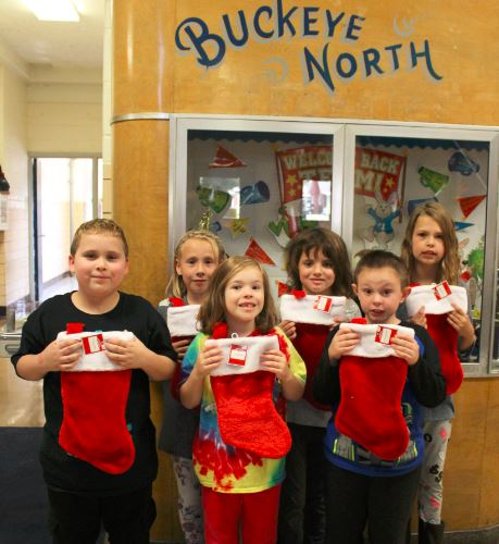 Pupils at Buckeye North Elementary will be collecting items for the annual Operation Christmas Stocking campaign through Boatsie's Boxes Inc. of Wheeling. Snacks and personal items will be accepted through early November and sent to military personnel serving overseas. Holding a few of the stockings are, front, from left, second-graders Damein Ohle, Zoey Ralston and Nola Toth; and back, Laney Cowden, Jakob Kendle and Myah Fabry. — Contributed
