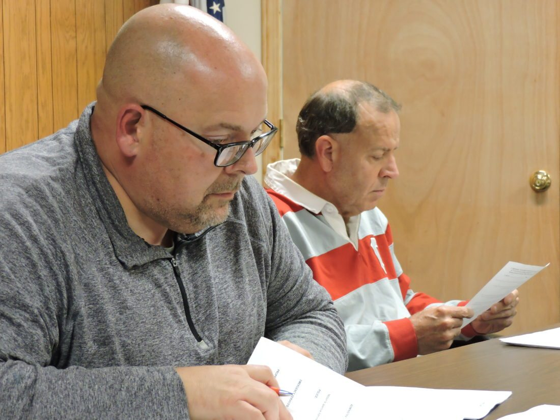 Cadiz Councilmen Mike McPeak, left, and Larry Sickle study an item during Thursday's meeting. — Dylan McKenzie