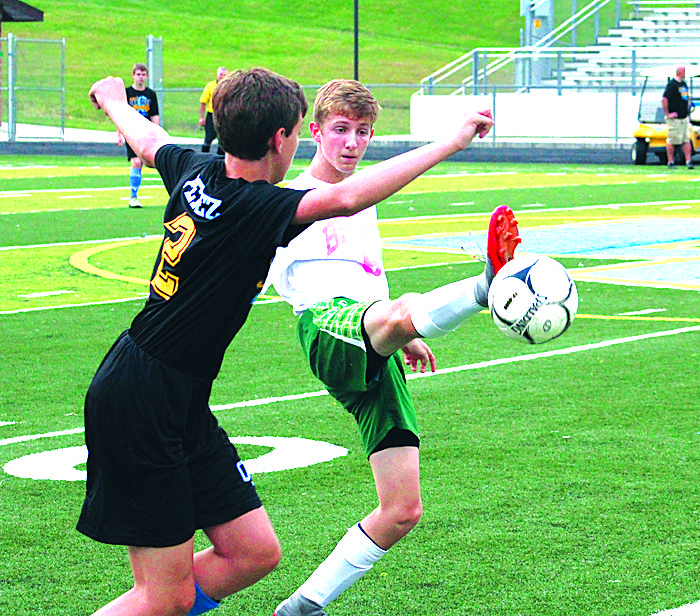 KICKINGAWAY — Brooke's Josh Ferguson kicks the ball out of the air away from Oak Glen's Blake Perez (Photo by Joe Catullo).