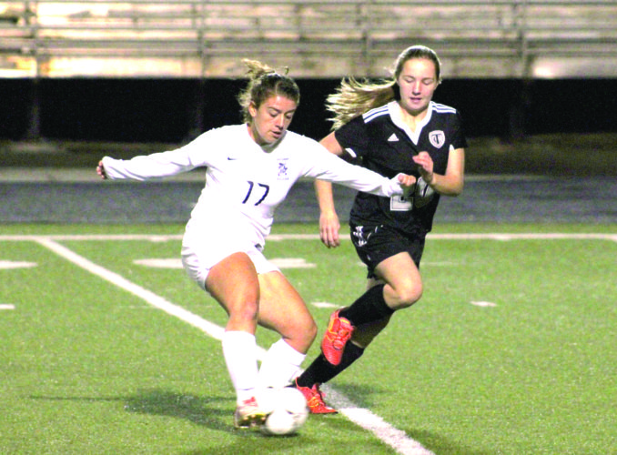 PASSING BY — Madonna's MaKayla Virden kicks in front of Tyler Consolidated's Kelsi Vandruff during a Class AA/A Region 1 Section 1 matchup on Monday at Brooke. (Photo by Joe Catullo)