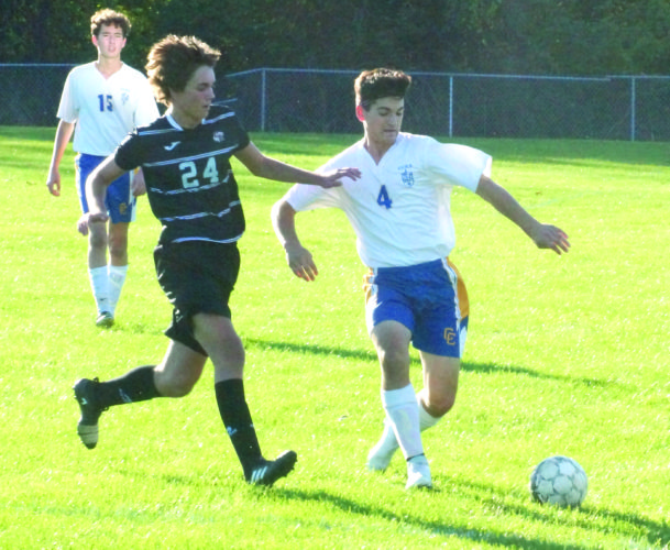 TAKING CONTROL — Steubenville Catholic Central's Ethan Moore (4) runs with the ball away from Coshocton's Guilermo Rodriguez  while Mark Kissinger (15) watches during a Division III sectional final on Wednesday. (Photo by Andrew Grimm)