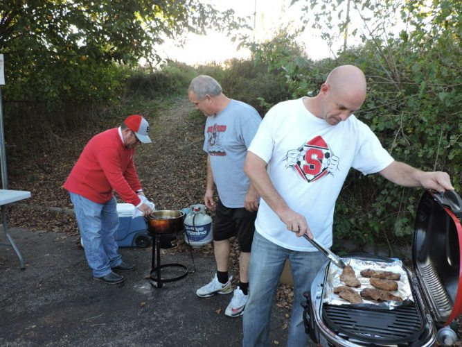 TAILGATING AT THE CROW'S NEST — Rob Biacco, left, checked on his fresh cut french fries while his cooking partner, Larry Carrocchi, right, grilled steaks while organizer Rick Crosier watched during the Crow's Nest tailgate party Friday night.