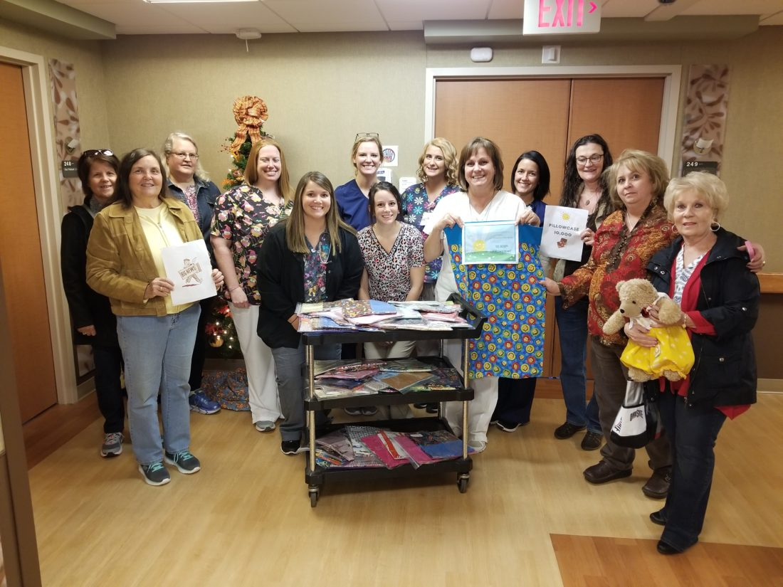 SPECIAL OCCASION — A recent donation of pillowcases to the pediatric department at Trinity West by representatives of Amazing Grace Pillowcases Inc. ministry included the 10,000th pillowcase made in the ministry's four-year history. On hand for the special occasion were, around the cart, from left, Tara Keenan; Alyssa Houk; and Janie Donahue, head of the pediatric floor; and back, sewing angel Tina Iarossi, holding sign; sewing angel Sue Smith; sewing angel Mary May; Ashley Virtue, Devon Kelly, Shannan Schramm and Ericka Crosier, pediatrics floor employees; LeAnn Leas, sewing angel; Mary Albaugh, founder of Amazing Grace Pillowcases Inc.; and Sandy Weiher, sewing angel.  -- Contributed