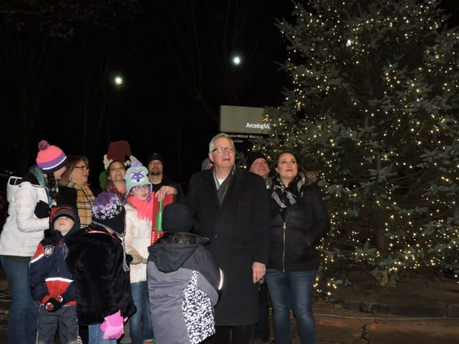 SPECIAL MOMENT — Joined by his family, Weirton Mayor Harold Miller watches as the community Christmas tree is lit and the fireworks display goes off overhead. Residents gathered at the Main Street and Pennsylvania Avenue intersection Sunday for the Weirton Light Up Night. -- Craig Howell