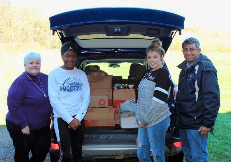 HELP AREA PANTRY — The Buckeye Local High School Fellowship of Christian Athletes donated nonperishable food to the Rush Run Community Chapel in Rayland to help fill the church pantry's Thanksgiving baskets. With the boxes are, from left, FCA adviser Belinda Boyce, President Shayauna Christian, Shelbey Anderson and the Rev. Jim Monogioudis.
