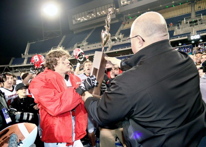 TROPHY PRESENTATION — Steubenville's Jacob Bernard receives the Division IV trophy on Saturday in Canton. Big Red defeated Clinton-Massie 50-36 to capture the title. (Photo by Michael D. McElwain)