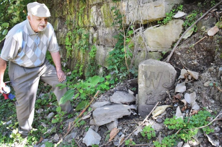"MARKER FOUND — Wheeling resident Robert ""Bob"" Lally shows where he found an old railroad marker nearly buried in the hillside along Heritage Trail. - Scott McCloskey"