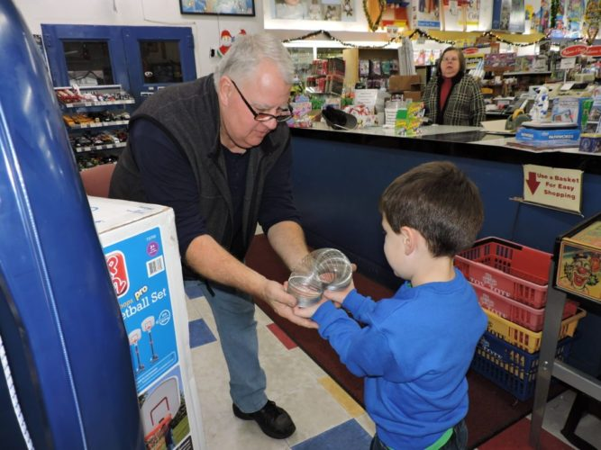 USA-MADE — Mike Yeso, owner of Deluxe Toys & Hobby in Martins Ferry, shows his 4-year-old grandson, Matty Kendall, how to play with a Slinky, one of the many USA-made toys at the shop. -- Shelley Hanson