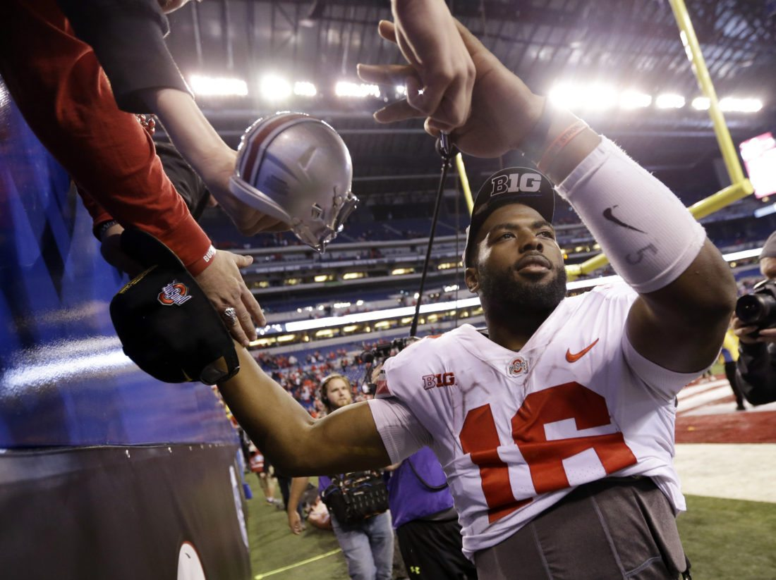 BIG TEN CHAMPS — Ohio State's J.T. Barrett celebrates with fans after his team stopped Wisconsin 27-21 to win the Big Ten championship in Indianapolis. - Associated Press
