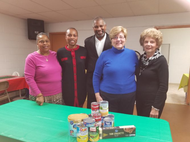 "DONATION MADE — Donations of food were presented to Pastor D. W. Cummings at the Church Women United's annual Christmas luncheon. The canned goods are for Bethlehem Apostolic Temple, Wheeling, and Shiloh Apostolic Faith Assembly, Weirton, pantries. On hand were, from left, Rebecca ""Tish"" Turner of the CWU; Pastor Cummings and his wife, Latisha Cummings; Cathy Cooper, president; and Diane Pastoric, citizens action chair. -- Contributed"