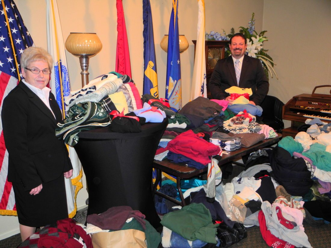 KEEPING VETERANS WARM — Ellen Daugherty, administrative assistant for Chambers and James Funeral Homes of Wellsburg and Follansbee, and Eric Fithyan, owner, stand among more than 300 sweaters, gloves and other clothing donated by area residents for veterans in local nursing homes and in a homeless shelter. Such community projects are among many criteria that have earned the funeral homes the National Funeral Directors Association's Pursuit of Excellence Award for three consecutive years.