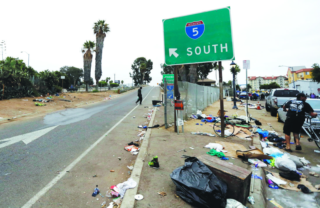 """HOMELESS WOES IN SAN DIEGO  — Trash from homeless encampments lines an entrance ramp for Interstate Highway 5 in San Diego. In a place that bills itself as """"America's Finest City,"""" renowned for its sunny weather, surfing and fish tacos, spiraling real estate values have contributed to spiraling homelessness in San Diego. Most alarmingly, the explosive growth in the number of people living outdoors has contributed to a hepatitis A epidemic."""