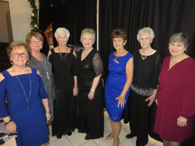 MODELS — The Wintersville Woman's Club held its 16th-annual Holiday Splendor fundraiser for scholarships on Dec. 3 at St. Florian Hall in Wintersville, which included a style show featuring fashions by the Dress Barn of Robinson Township. Woman's club members serving as models were, from left, Tyra Timmons, Marjean Sizemore, Aimee Jaros, Robbie Young, Judy Weaver, Ella Jane Burns and Joan Doan. They are shown in evening wear but also modeled casual and business clothing. -- Janice Kiaski