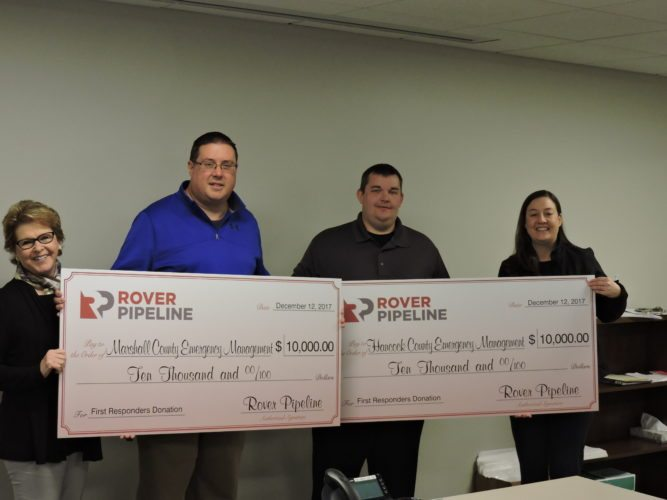 Rover Pipeline representatives Susan King, left, and Alexis Daniel, right, presented checks to Marshall and Hancock County OEM directors Tom Hart, second from left, and Jeremy Oberman. — Alan Olson