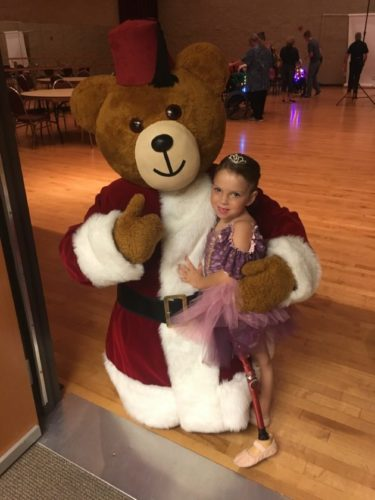 IN COMMERCIAL — Sarah Czapp, 6, is shown with Fezzie, the Shriners Hospitals for Children mascot, during a break in filming of the national Christmas commercial in August in St. Louis.