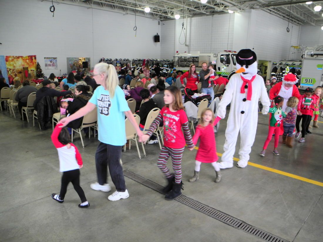 ENJOYING THE PARTY — Many area children joined Frosty the Snowman and Mrs. Claus in dancing to Christmas music played by Kenny Wells at the 39th annual Ray Laman Christmas Party Saturday at the Wintersville Fire Department. Santa Claus also met with children at the event, which was supported by many businesses, citizens and groups. - Staff photo