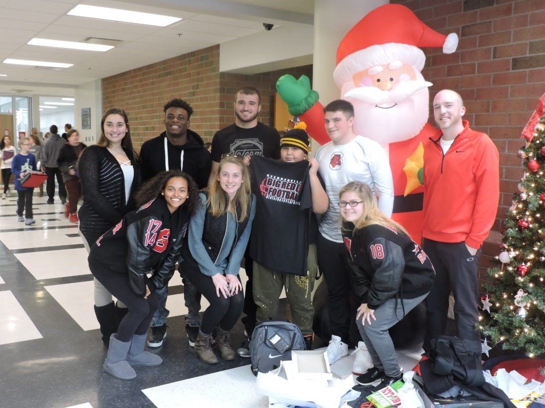MERRYCHRISTMAS — Members of the Steubenville High School Interact Club gave Harding Middle School pupil Victor Anway a special Christmas Tuesday afternoon. Taking part in the gift-giving were, front, from left, Makayla Crownover,  Suzie Rosaschi, Anway, Seana Ragusa, Ty Artesic and Interact Club adviser Scott Lane; and back, Maggie Fabian, Dajuan Jones and Johnny Agresta. -- Dave Gossett